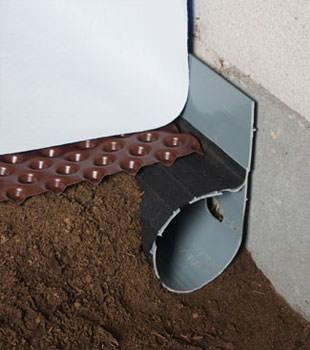 Closeup of a crawl space drainage system installed in Indianola